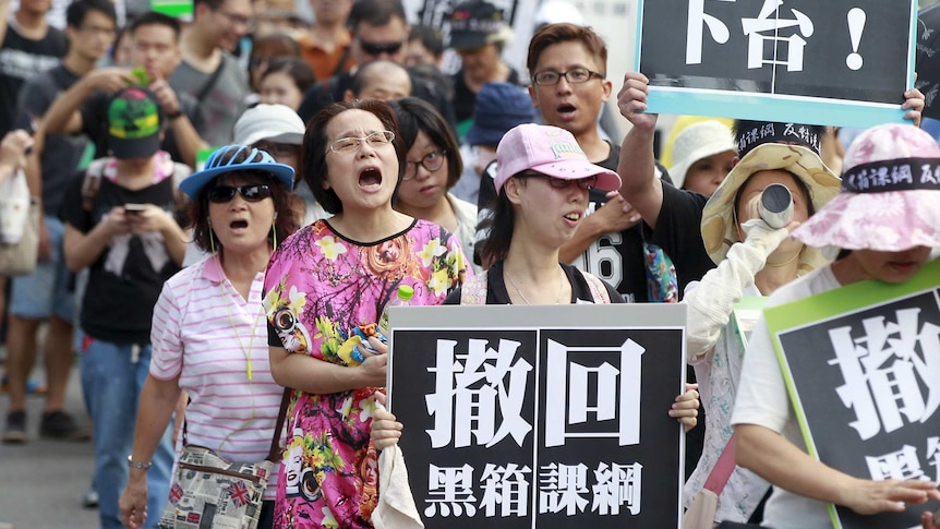 Activists march in front of Taiwan's education ministry