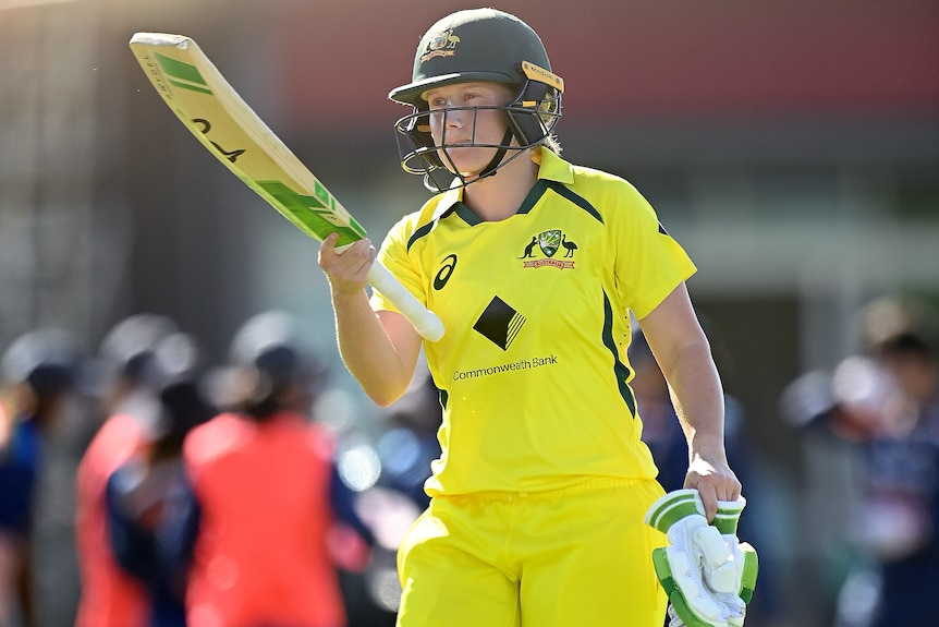 An Australia female cricketer raises her bat after being dismissed against India.