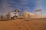 A white road train passing through a gate on a red dirt road
