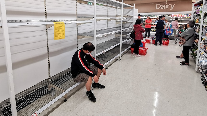 People waiting in the toilet paper aisle for a delivery of toilet paper, paper towel and pasta at Coles Supermarket.