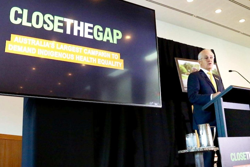 Malcolm Turnbull speaks at a podium, with the Closing the Gap projected onto a screen next to him.