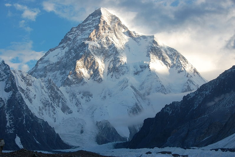 K2 appears in front of a blue sky with sun and some cloud cover