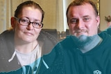 A young couple with a rising blue line graph superimposed over them.