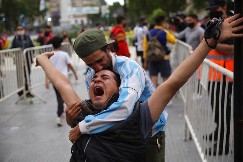 A football fan cries in the street.