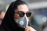 A woman wears a black medical mask.