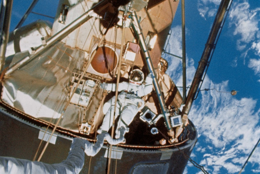 Astronaut Edward Gibson performs a space walk on Skylab space station.