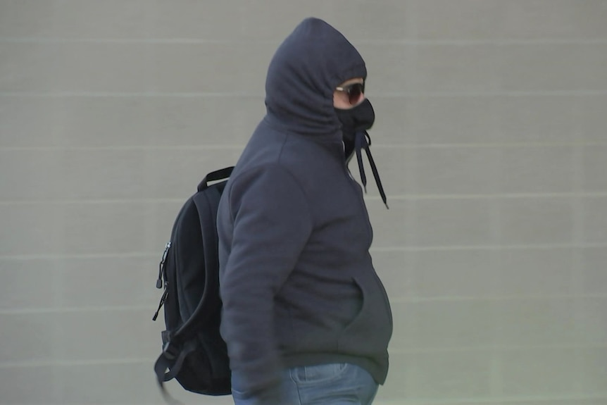 A man wearing a black hoodie tied around his face and sunglasses.