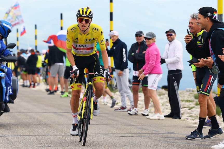 The Tour de France overall leader in the yellow jersey grimaces as he rides alone during a stage.