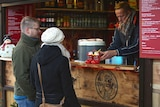 A couple purchase drinks from a market stall.
