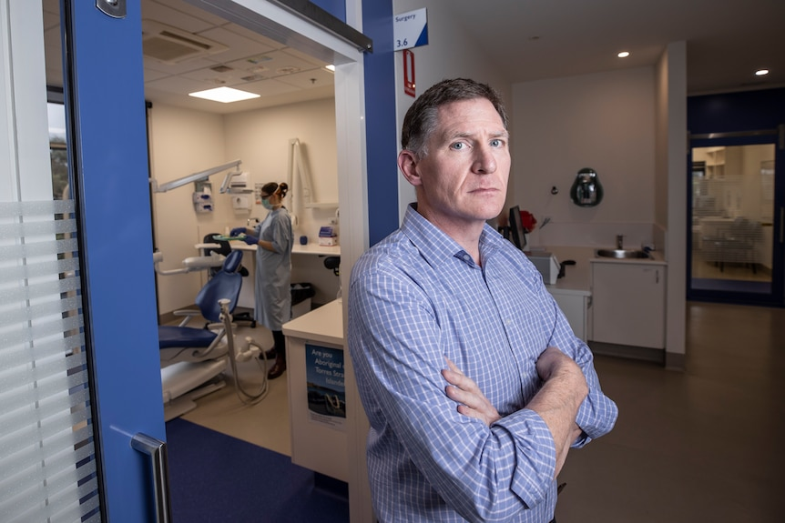 A man with his arms folded standing in front of a dental room.