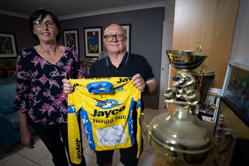 A smiling couple look at the camera holding their son's cycling jersey, standing next to trophies.