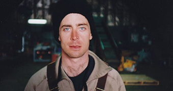A man wearing work clothes and a black beanie, with bright blue eyes, stares towards the camera with a serious expression.