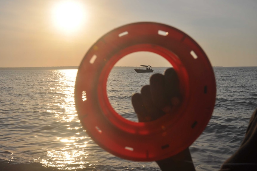 A fishing reel held up to the sun by a young Aboriginal person's hand.