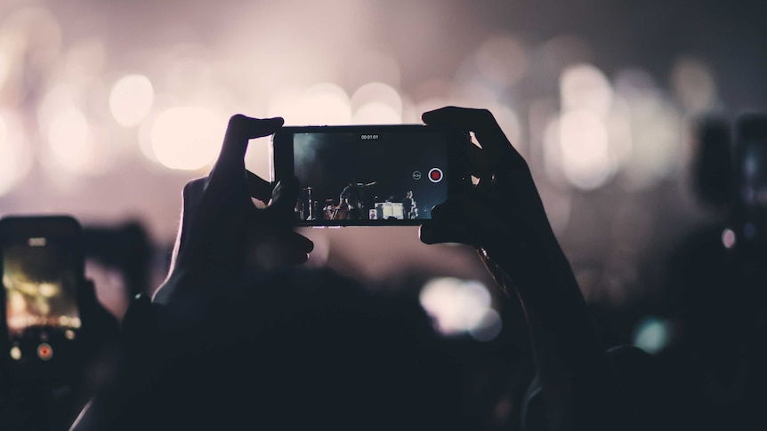 Hands hold up a phone at a gig