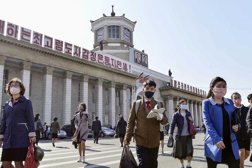 People in face masks walk outside a train station in Pyongyang