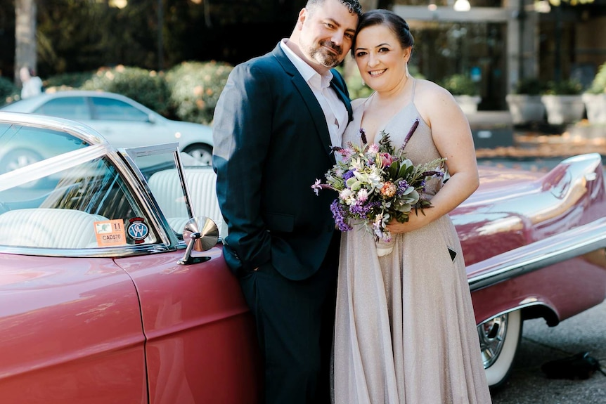 A woman in a long pale grey dress holds a bunch of flowers and stands close to a man in a suit with a red vintage car behind