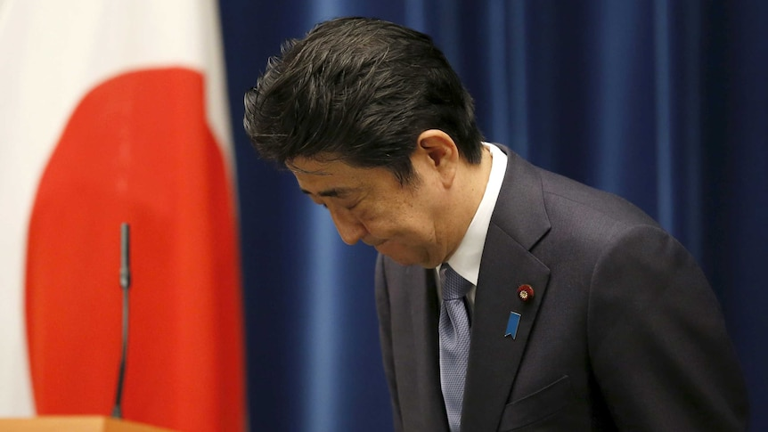 Japan's prime minister Shinzo Abe bows as he leaves a news conference