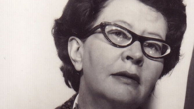 A close up sepia toned photo of Coral Bell, a woman with dark short hair in cats eye spectacles