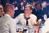 An AFL player sits with his jacket off and his hand over his mouth as he takes in the count at the Brownlow medal.