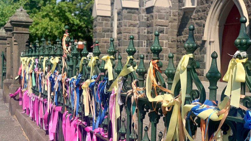 A close up of hundreds of colourful ribbons tied to a fence outside a church
