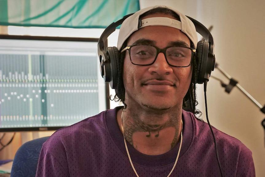 A man wearing head phones sits in his music studio