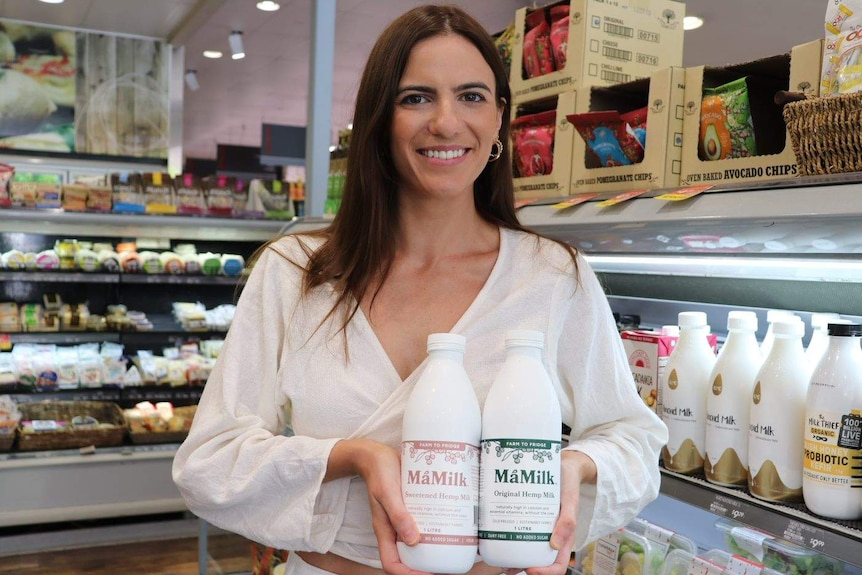 Tegan Scates from MaMilk holds two bottles of cold pressed hemp milk at a Brisbane supermarket.