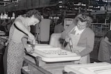 A black and white photo of two women drilling into fridge doors in the Emmco factory in 1956.