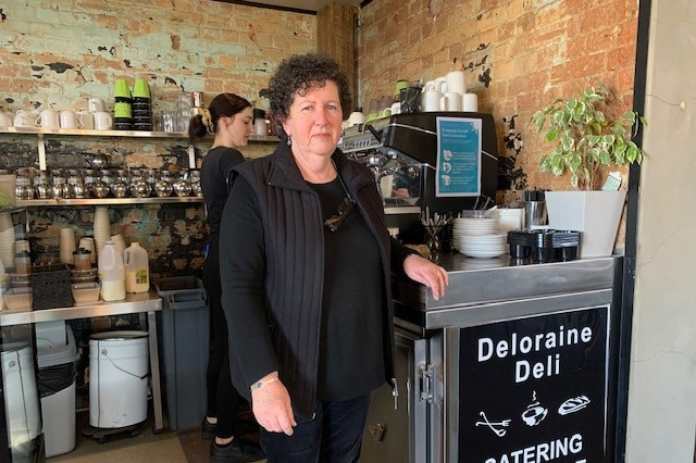 Business owner standing at cafe counter