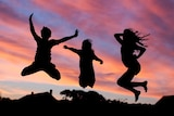 Silhouettes of happy children playing and jumping into the air at sunset.