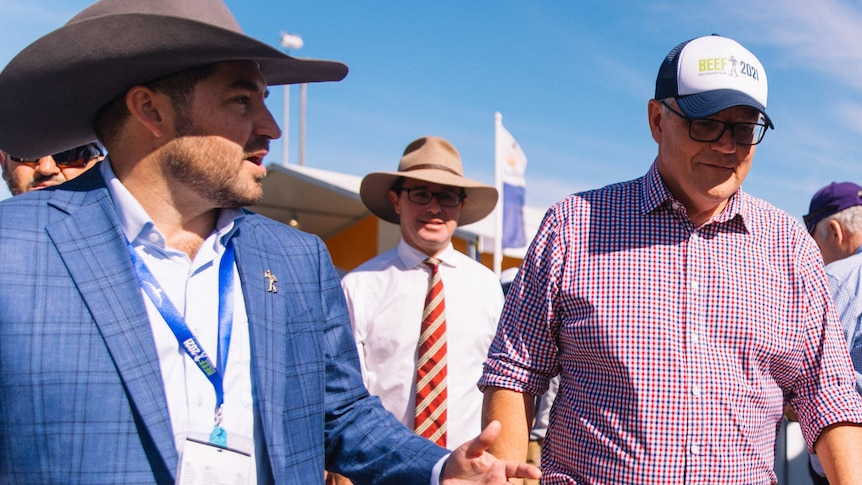 Mid shot of a man in a large cowboy hat speaking to Prime Minister Scott Morrison