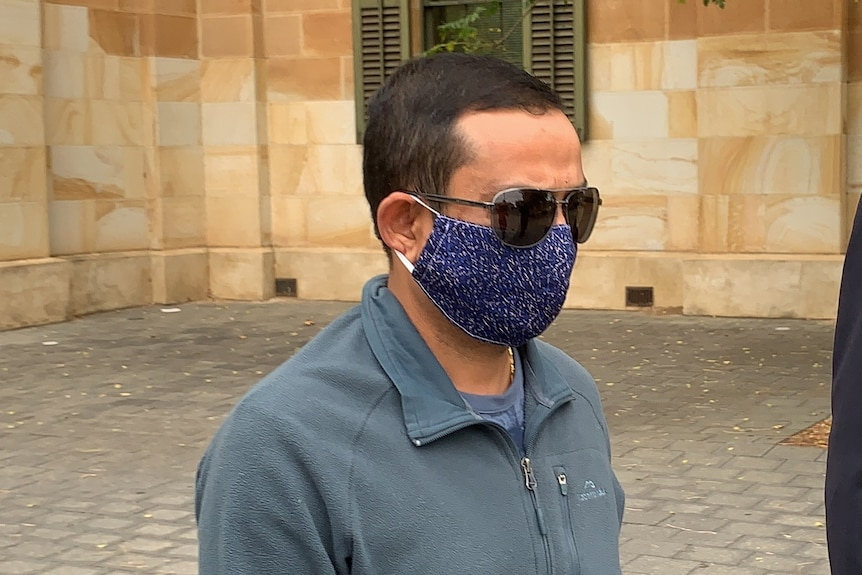 A man with short dark hair wearing sunglasses and a blue spotty face mask