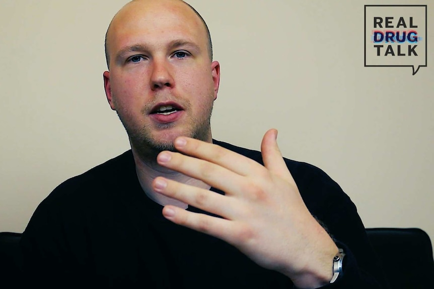 A man with a shaved head gestures