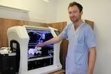 Orthopaedic surgeon Dr Jonathan Davis holding a 3D printed bone inside Mackay Base Hospital's first 3D printer.