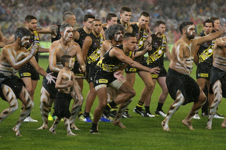 Sydney Stack is front and centre, surrounded by painted Indigenous men and followed by his teammates, doing a traditional dance