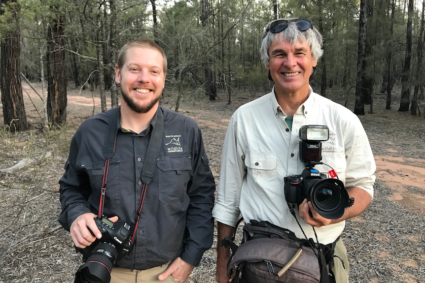 Two men with digital SLR cameras around their necks stand in a dry forest.