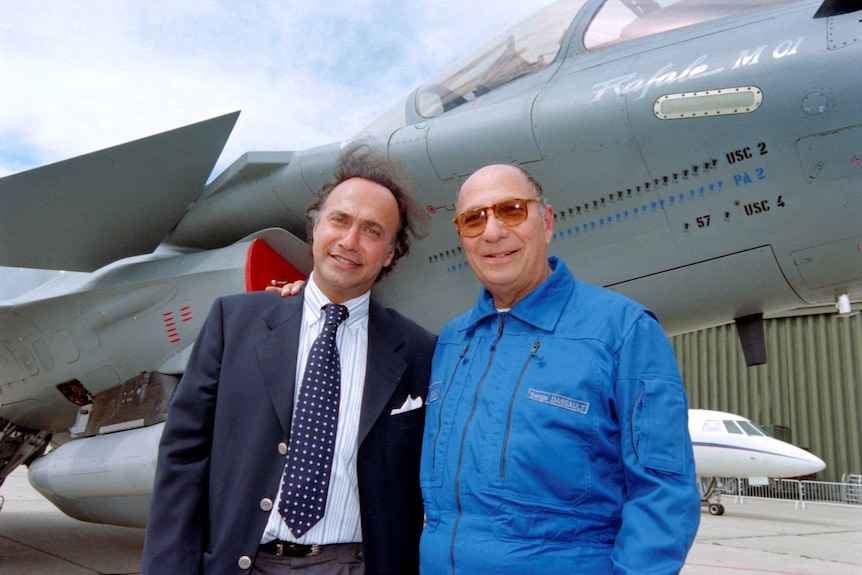 Olivier Dassault and his father Serge pose in front of a fighter jet