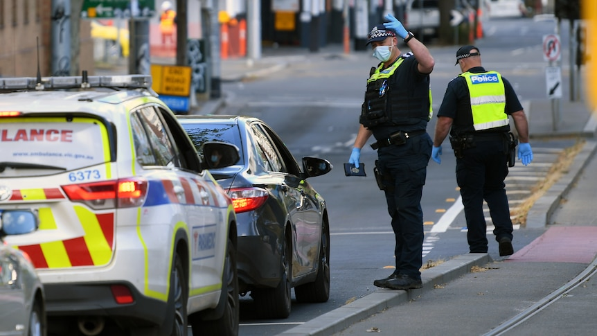 Victorian Police officers speak to a person in a car at a Police checkpoint.