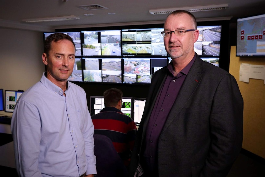 Two men stand in front of traffic monitoring screens, another man sits with his back to the camera
