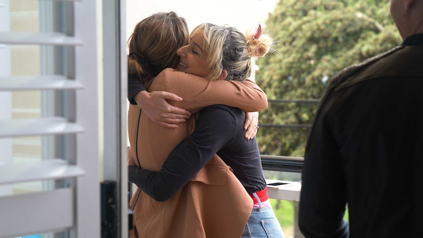 A woman hugs her friend as she enters a weekend barbeque, grateful for support and friendship as she prepares for an IUI attempt