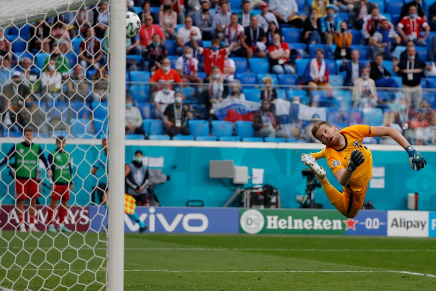 A goalkeeper twists in mid-air as he watches the ball fly past him into the top corner during a Euro 2020 game.