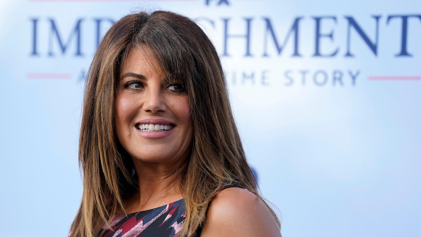Monica Lewinsky smiles and looks over her shoulder while standing in front of a promotion for Impeachment.