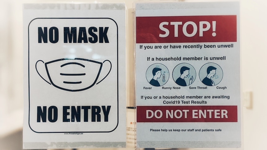 A sign warning people to wear masks and not to enter if they are feeling unwell.