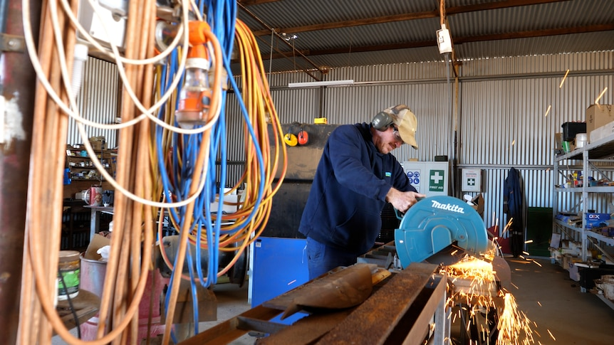 Chapman Valley farmer Brady Green welding in his farm shed with power cords in the foreground.