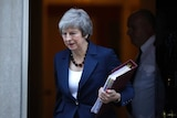 Theresa May carries a folder as she leaves 10 Downing St