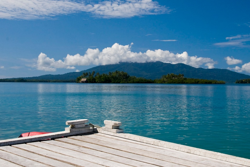 Looking from a wooden jetty, you few tranquil turquoise waters with a mountain sitting on the horizon line.