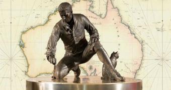 Brass Matthew Flinders statue on podium bent over with cat Trim against background map of Australia.