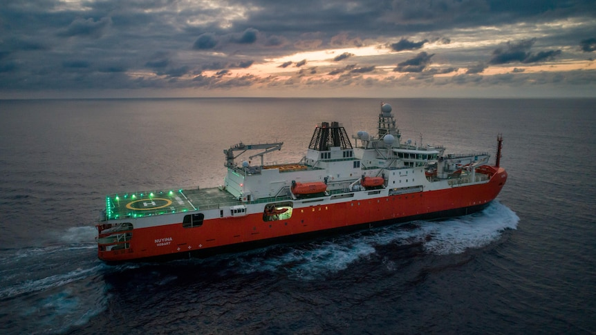 Ship at sea in dawn light, with helicopter pad light up on deck