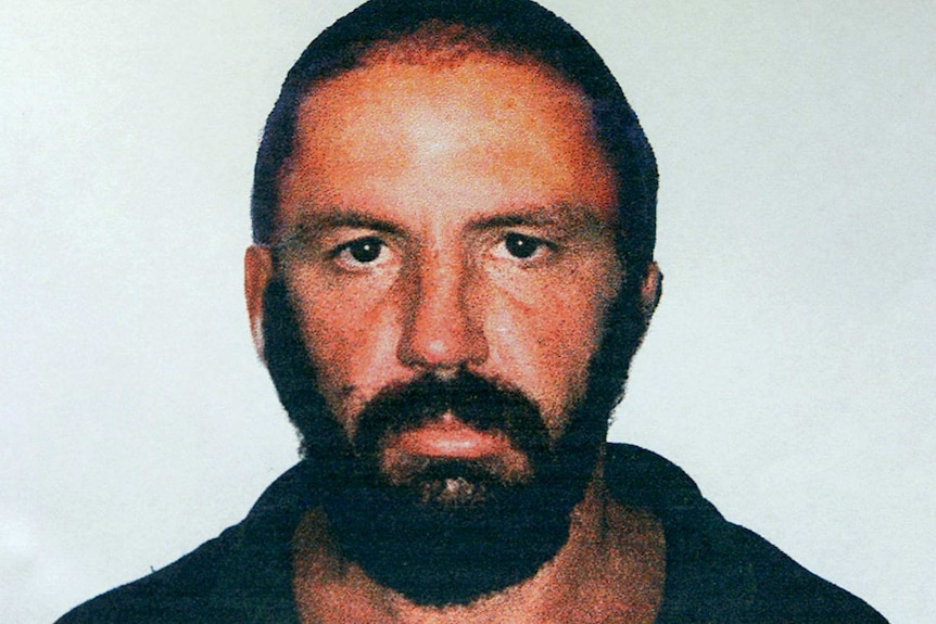 Mugshot of Robert Paul Long in 2000. Man wears crew cut and thick beard and looks directly at camera