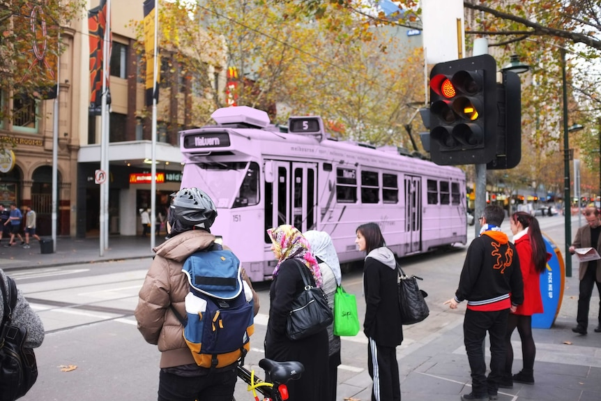 People in Melbourne street spending their time commuting, while a tram travels through.
