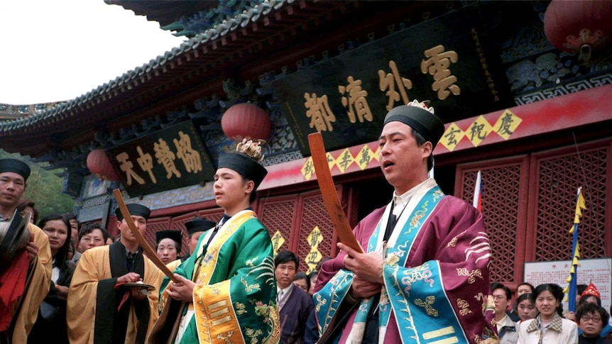 Daoist priests conduct prayers for a group of elderly pilgrims